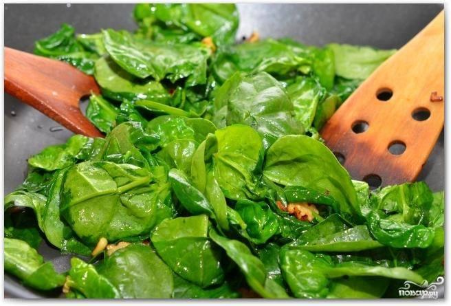 Следом за орешками кладем в сковороду шпинат. Перемешивая, тушим около 1 минуты, максимум - 2 минуты. Нам нужен слегка размякший шпинат - для этого достаточно 1 минуты на сковороде.