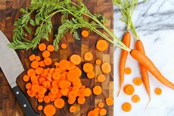 1. Морковь очистите, нарежьте тонкими кружочками. Выложите в кастрюлю с кипящей водой и проварите 4-5 минут до мягкости. Важно не переварить, что морковь оставалась немного хрустящей. Снимите с огня и слейте воду, добавьте мелко нарезанный лук.