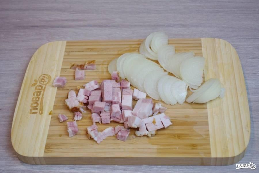 Пока картофель варится, нарежьте бекон кубиками, а репчатый лук полукольцами.