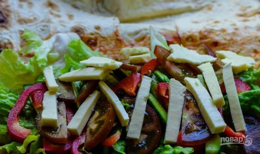 Выложите на лаваш, смазанный заправкой, листья салата, полоски болгарского перца и огурцы. Вымойте томаты, нарежьте их кусочками и выложите поверх овощей. Посыпьте все перцем и солью. Затем добавьте адыгейский сыр, нарезанный брусочками.