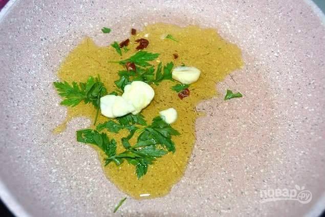 В сковороде нагрейте оливковое масло и слегка обжарьте, до появления аромата, мелко нарезанный чеснок и острый перец с рубленой петрушкой.
