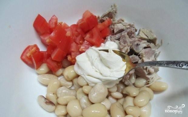 2. Помойте помидор. Подсушите его бумажным полотенцем. Порежьте кубиками. Выложите в салатницу фасоль, свинину и помидор. Соедините майонез со сметаной. Заправьте салат.