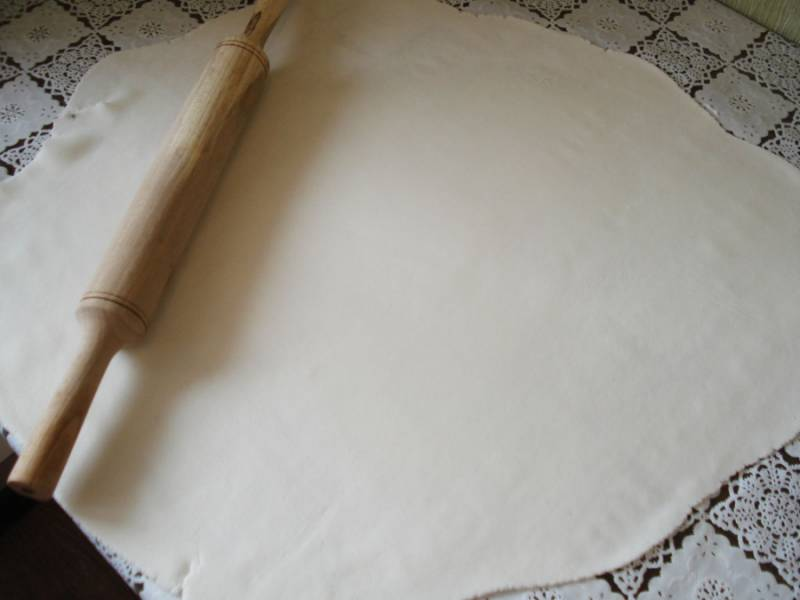 Мастику раскатываем в тонкую лепешку, предварительно посыпав сахарной пудрой стол и скалку. Накрываем лепешкой торт, излишки мастики срезаем острым ножом.