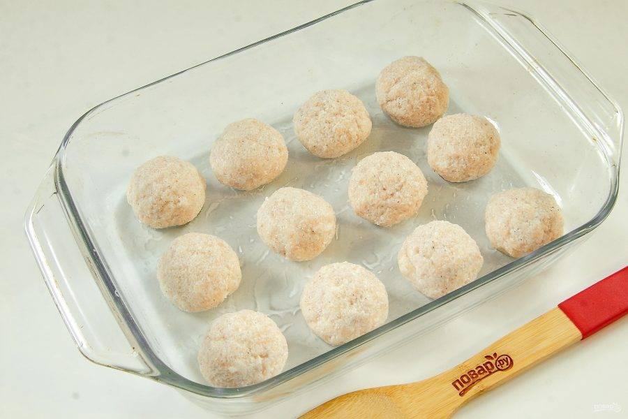 Смажьте руки растительным маслом и сформируйте из фарша небольшие шарики. Выложите их в форму для запекания.