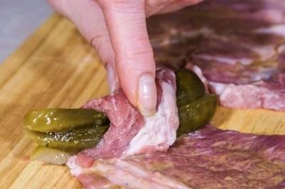 2. Огурцы нарезаем соломкой, и заворачиваем в  каждый кусочек мяса.