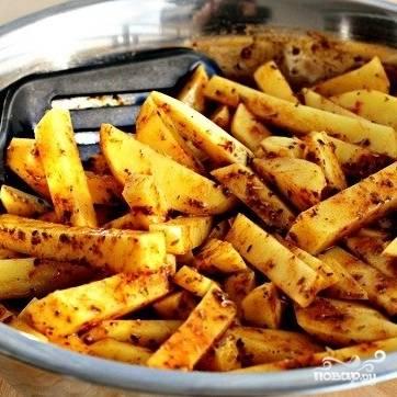 Добавляем специи, хорошенько перемешиваем, чтобы специи равномерно смешались с картофелем.