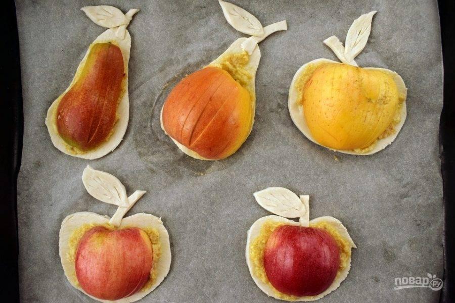Фрукты нарежьте на половинки, удалите семенные коробочки. На половинках сделайте продольные надрезы, не доходя до низа 5 мм, и положите их сверху заготовок теста, слегка прижмите. Сверху фрукты смажьте ореховым кремом, тесто — слегка взбитым яйцом. Поставьте пирожные запекаться в разогретую духовку на 15-20 минут.