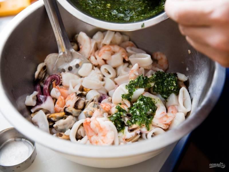 Кинзу измельчаем вместе с зубчиком чеснока, смешиваем с маслом и лимонным соком. Все морепродукты, кроме мидий, складываем в одну миску, заливаем их заправкой.