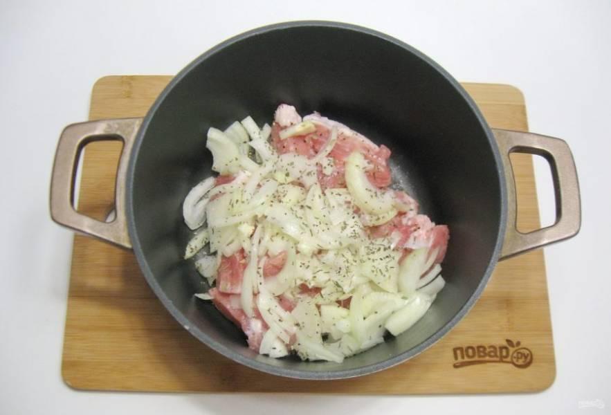 В казан или кастрюлю с толстым дном выложите мясо и лук. Посыпьте немного солью и базиликом.