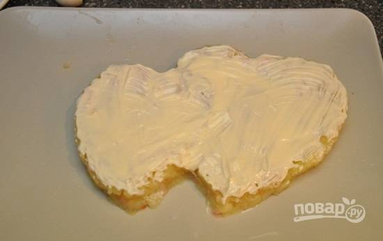 Теперь самое сложное: необходимо выложить первый слой из картофеля в форме двух сердец. Одно побольше, а другое поменьше размером. Посолим и смажем майонезом.