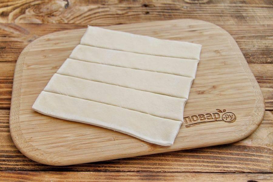 Тесто разморозьте, если оно замороженное. Немного раскатайте в одном направлении и нарежьте тесто на полоски, шириной 4-5 см. Если необходимо, немного посолите тесто по вкусу.