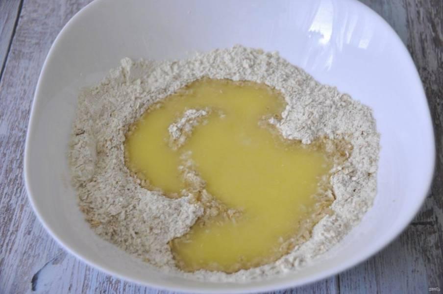 В сухую смесь влейте воду и масло с медом.