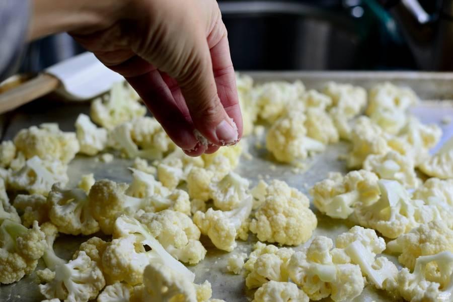 Шаг 2. Разберите их на соцветия. Выложите на противень. Присыпьте щепоткой соли и полейте  оливковым маслом.