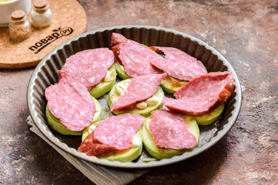 Колбасу выбирайте самую вкусную. Нарежьте колбасу щедрыми кусочками и выложите поверх кабачков. Для диетического варианта используйте сметану и вареное куриное филе.