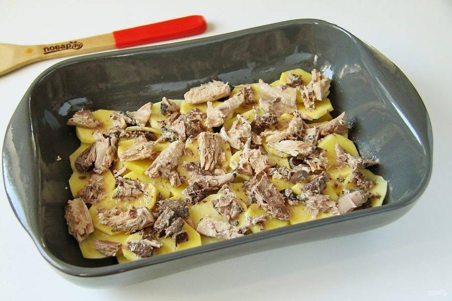 Тунец слегка разомните вилкой и разложите равномерно на картофель.