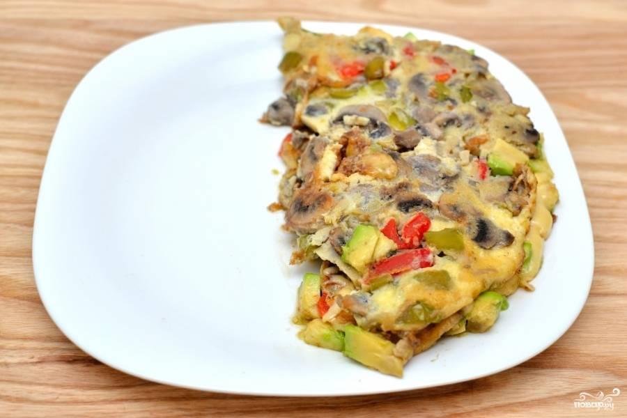 Сложите омлет с сыром и овощами вдвое. Подавайте к столу.