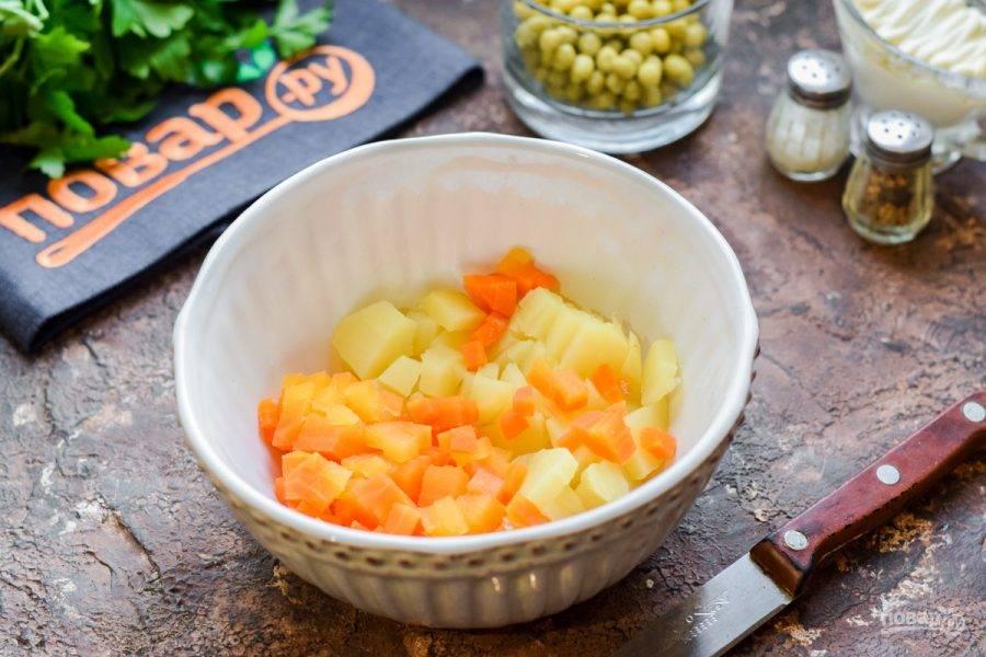 Очистите картофель и морковь, нарежьте небольшими кубиками и переложите в салатник.