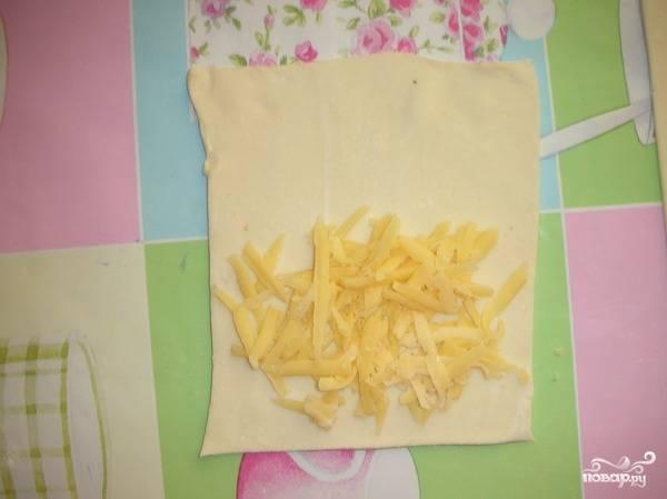 Тесто тонко раскатываем и разрезаем на прямоугольники. На половинку прямоугольника выкладываем сыр, и здесь главное не переборщить, а то начинка будет вытекать в духовке и пригорать к противню.