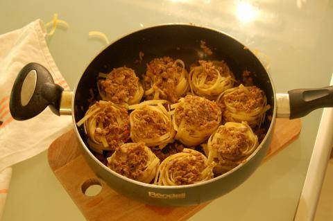 Затем гнезда фаршируем и укладываем в глубокую сковороду и заливаем водой до краев гнезда.