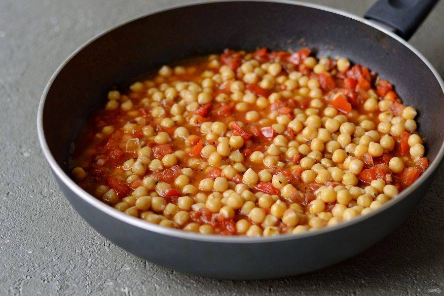 Затем добавьте в сковороду нут, перемешайте и тушите на маленьком огне полчаса. Периодически подливайте воду, в которой варился нут. Варите нут до мягкости.