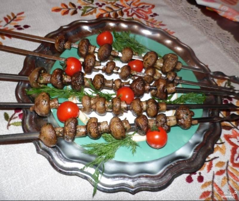 На мангале с углями грибы на шампурах нужно жарить около 30-40 минут. Втечение этого времени шампуры несколько раз переворачивайте, чтобы грибы пропеклись со всех сторон. На грибы периодически наливайте маринад, который остался в тарелке.