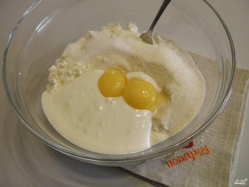 Смешайте в глубокой посудине манку с сахаром, творогом, сметаной и желтками яиц.