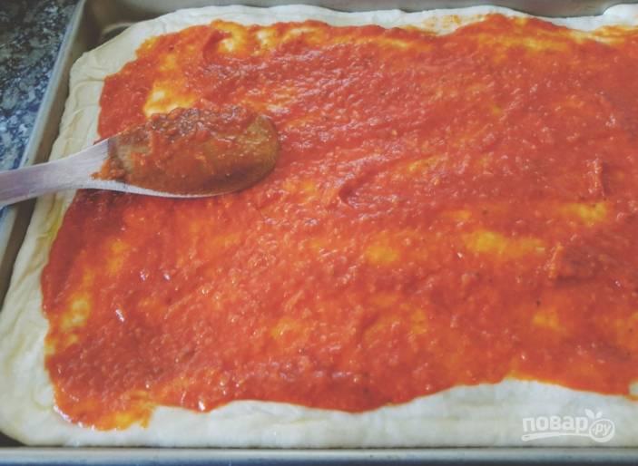 Затем тесто смажьте томатным соусом, по желанию присыпьте сушеным базиликом.