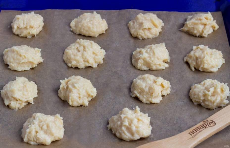 Выложите тесто на противень с пекарской бумагой столовой ложкой или с помощью кондитерской насадки.