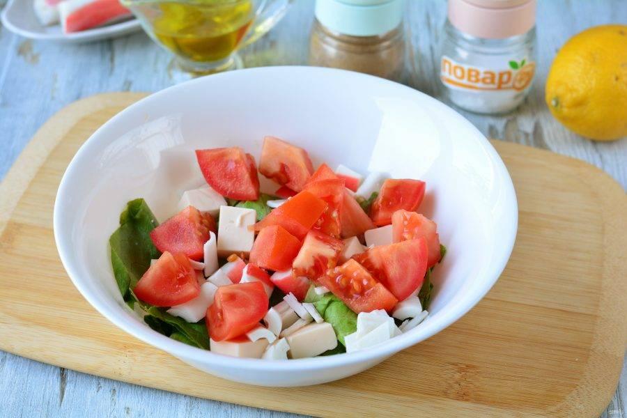 Нарежьте помидоры средними кусочками и выложите в салат.