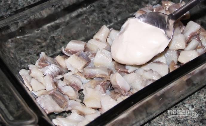 3.В салатник или любое другое глубокое блюдо выкладываю нижним слоем селедку. Смазываю рыбку тонким слоем майонеза.