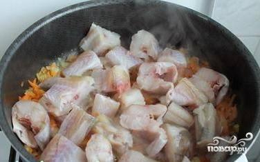 Минтай очищаем, промываем, просушиваем, нарезаем небольшими кубиками или кусочками, добавляем к овощам, перемешиваем. Накрываем крышкой и тушим около 5-7 минут.