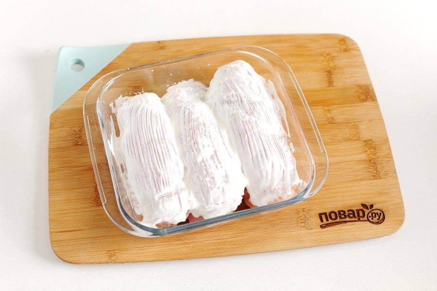 Смажьте рулетики сметаной и запекайте в духовке при температуре 180 градусов около 30 минут. На первые 10-15 минут форму можно накрыть фольгой.