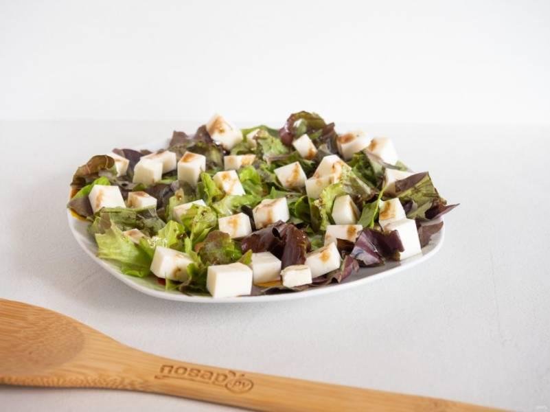 Брынзу нарежьте кубиками и выложите на салат. Тоже полейте соусом.