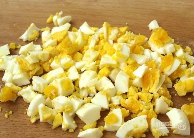 В отдельную кастрюлю положите сырые куриные яйца, залейте их холодной водой и поставьте на плиту. Варите яйца десять минут. Затем остудите под проточной холодной водой и очистите от скорлупы. Нарежьте яйца кубиками.