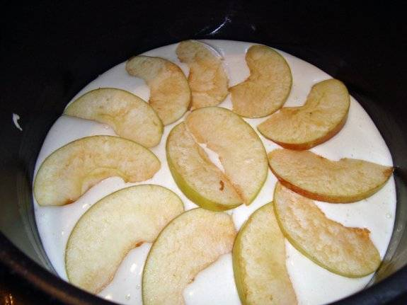 Теперь выливаем в чашу остальную часть теста, выкладываем на поверхности яблоки.