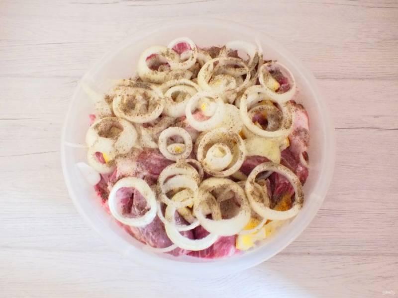 Следующий слой выложите из лука и лимона и так далее чередуйте с кусками мяса. Верхним слоем должны быть лук и лимон. Поперчите и помните руками мясо с луком и лимоном.