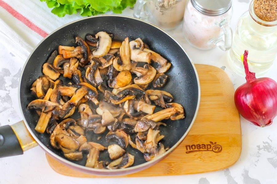 Шампиньоны промойте в воде и нарежьте слайсами. Прогрейте в сковороде растительное масло, выложите в него грибную нарезку, посолите и обжарьте примерно 2-3 минуты до румяности. Дайте остыть.