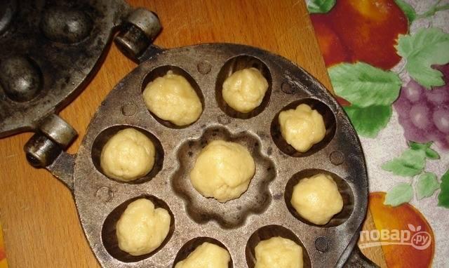 Орешки необходимо делать при помощи специальной формы. Разогрейте ее на конфорке, смажьте растительным маслом и выложите в полые отверстия по кусочку теста. Прижмите и подержите над конфоркой по пять минут с обеих сторон.