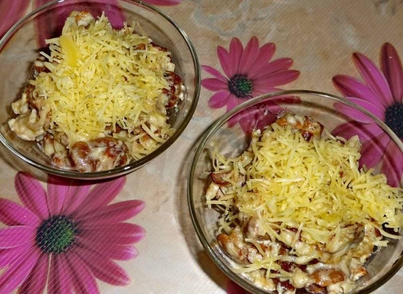 Раскладываем грибы вместе с соусом по формам, лучше всего, конечно, взять кокотницы, но можно использовать и другую огнеупорную посуду. Сверху лисички посыпаем тертым на крупной терке твердым сыром и ставим формы в разогретую до 180 градусов духовку на 5 минут.