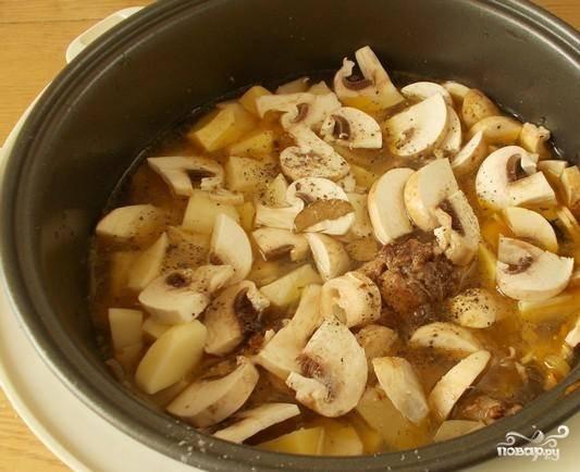"""Почистите и вымойте клубни картофеля, порежьте его кубиками. Добавьте картошку и грибы в чашу мультиварки и залейте все водой. Поставьте режим """"Тушение"""", бросьте лаврушку, соль и специи. Томите блюдо полтора часа до полной готовности."""