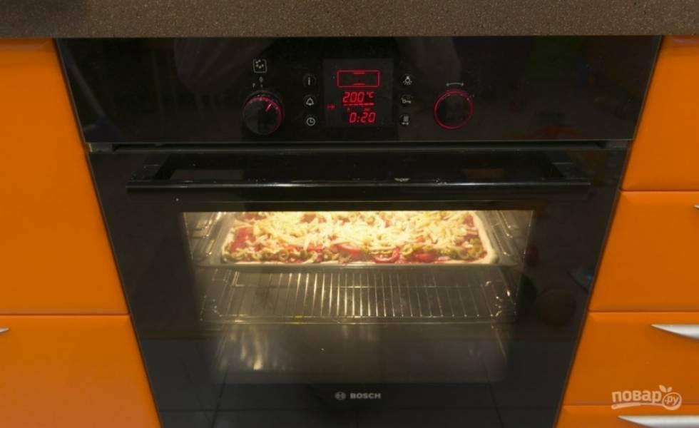 Ставим пиццу в духовку на 15 минут. После достаем противень и натираем на пиццу сыр. Затем отправляем ее в духовку еще на 5-8 минут.