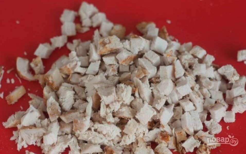 Когда куриное филе остынет, освободите его от фольги. Затем нарежьте куриное мясо на мелкие кубики.