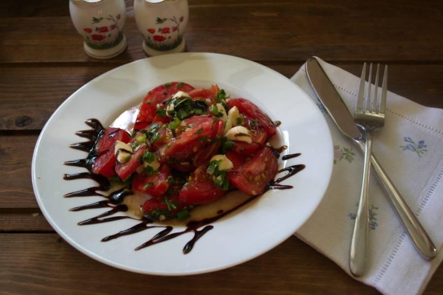 Помидоры посолите и поперчите по вкусу. Еще раз перемешайте.Выложите помидоры горкой поверх рисунка. Сделайте  еще несколько штрихов бальзамическим кремом уже на помидорах. Подавайте к столу.