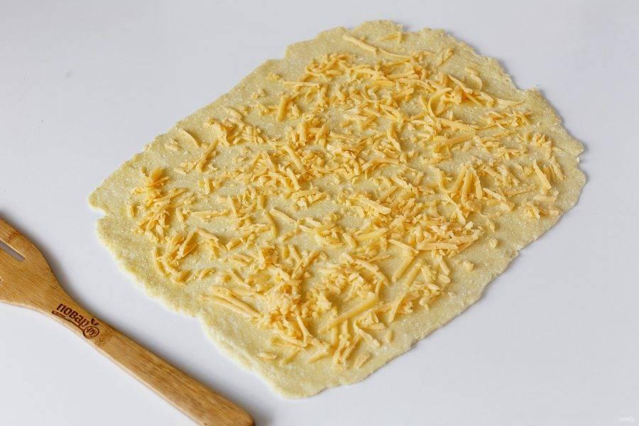 Смажьте рабочую поверхность растительным маслом и раскатайте тесто в форме прямоугольника. Сверху посыпьте тесто тертым сыром.