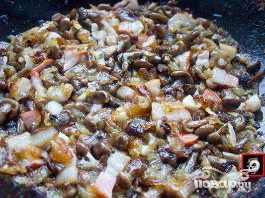 2.Вначале поджариваем лук, добавляем в него копченого бекону и обжаренных опят. Следует поперчить и посолить начинку.