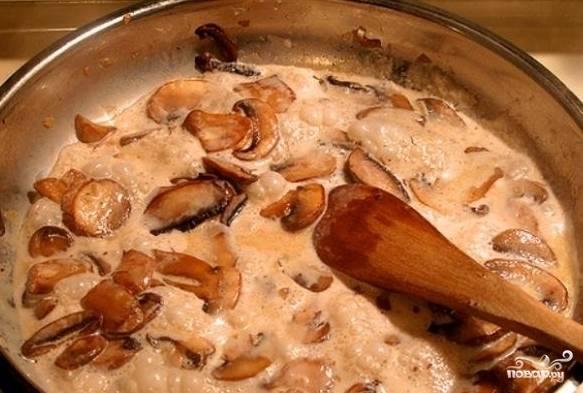 Заливаем грибы с луком сметаной, уменьшаем огонь до минимума и готовим под крышкой 10-15 минут.