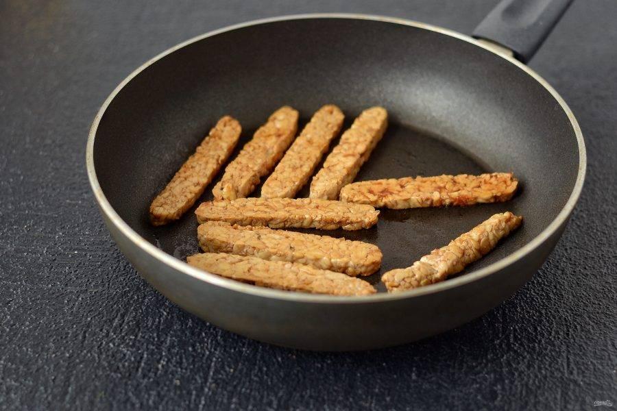Темпе нарежьте полосками в полсантиметра. Окуните в соевый соус и обжарьте на сковороде с двух сторон до коричневой корочки.