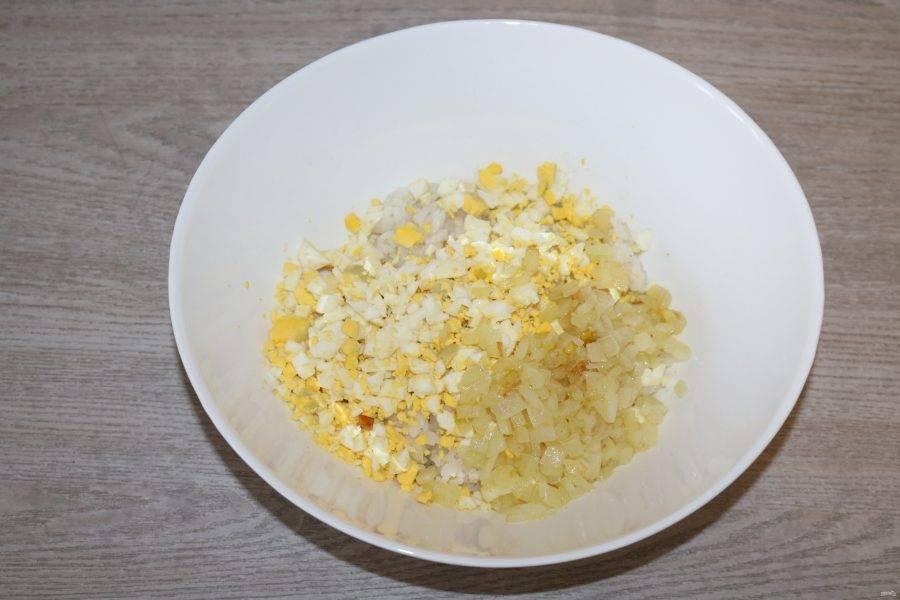 В миске соедините отварной рис, нарезанные яйца, обжаренный лук.