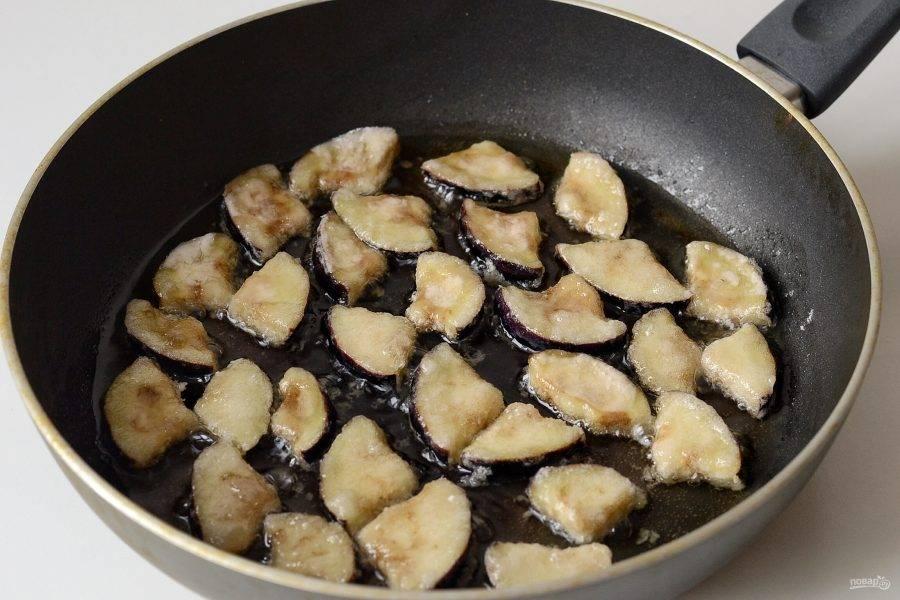 Обжарьте ломтики баклажанов в большом количестве масла до хрустящей корочки. Затем выложите на бумажное полотенце.