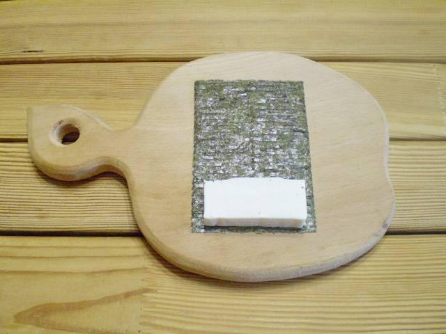 6. Кладем на влажный лист нори кусочек сыра, заворачиваем. Нори лучше приклеиваются когда чуть влажные, но не слишком мочите, чтобы не испортить водоросли.
